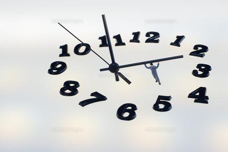 複数の光の中の時計とミニチュアの人のシルエットの写真素材 [FYI04667523]