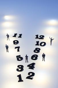 複数の光の中の数字と五つのミニチュアの人のシルエットの写真素材 [FYI04667525]