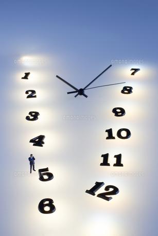 複数の光の中の時計とミニチュアの人のシルエットの写真素材 [FYI04667528]