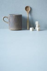 コーヒーカップと木のスプーンと積み重なった角砂糖の写真素材 [FYI04667809]