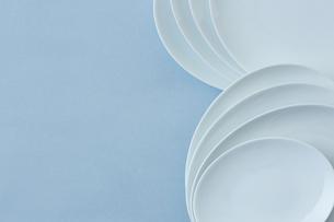 重ねた白い皿と水色の背景の写真素材 [FYI04667811]