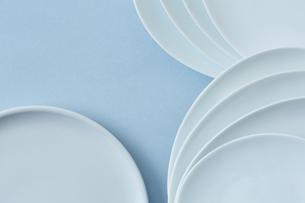 重ねた白い皿と水色の背景の写真素材 [FYI04667812]