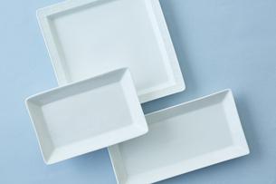 重ねた四角い白い皿と水色の背景の写真素材 [FYI04667814]