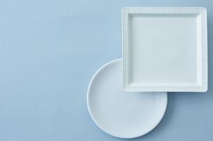 重ねた四角と丸の白い皿と水色の背景の写真素材 [FYI04667815]