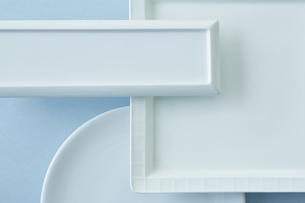 重ねた四角と丸の白い皿と水色の背景の写真素材 [FYI04667816]
