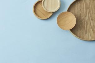 重ねた木の皿と水色の背景の写真素材 [FYI04667818]
