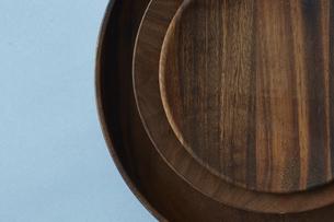重ねた木の皿と水色の背景の写真素材 [FYI04667821]