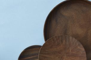 重ねた木の皿と水色の背景の写真素材 [FYI04667822]