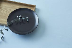 四角の木のトレイと黒い丸の皿に添えたユーカリの写真素材 [FYI04667824]