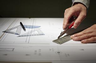 カッターで作業する男性の手の写真素材 [FYI04668608]