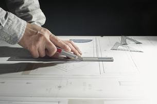 カッターで作業する男性の手の写真素材 [FYI04668612]