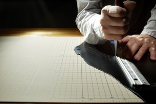革を切る男性の手の写真素材 [FYI04668616]