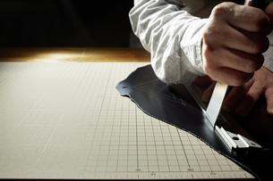 革を切る男性の手の写真素材 [FYI04668617]
