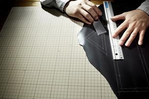 革を切る男性の手の写真素材 [FYI04668618]