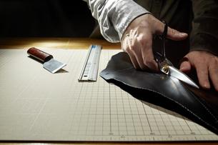 革を切る男性の手の写真素材 [FYI04668619]