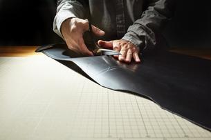 革を切る男性の手の写真素材 [FYI04668620]