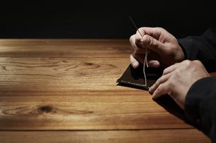 革を縫う男性の手の写真素材 [FYI04668626]