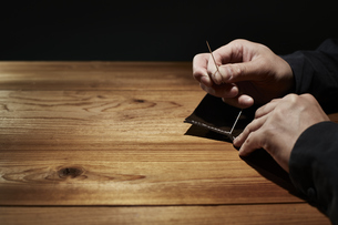 革を縫う男性の手の写真素材 [FYI04668627]