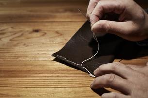 革を縫う男性の手の写真素材 [FYI04668629]