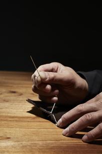 革を縫う男性の手の写真素材 [FYI04668631]