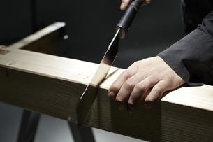 材木を切る男性の手の写真素材 [FYI04668644]