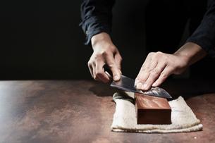 包丁を研ぐ男性の手の写真素材 [FYI04668667]