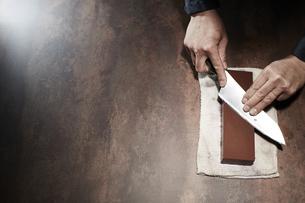 包丁を研ぐ男性の手の写真素材 [FYI04668668]