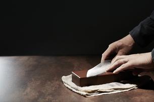 包丁を研ぐ男性の手の写真素材 [FYI04668669]