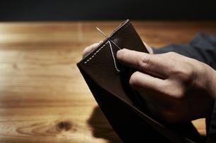 革を縫う男性の手の写真素材 [FYI04668670]