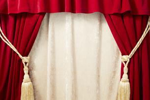 タッセルが付いているベロアの赤いカーテンの写真素材 [FYI04668691]
