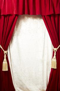 タッセルが付いているベロアの赤いカーテンの写真素材 [FYI04668692]