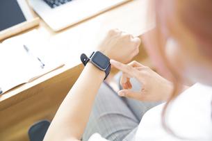 自宅オフィスでスマートウォッチを見る女性の写真素材 [FYI04669973]