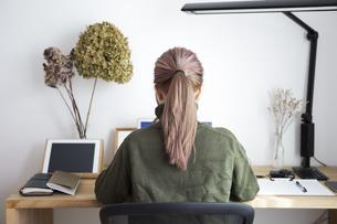 自宅オフィスでリモートワークで働く女性とデスク用品の写真素材 [FYI04669988]