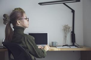 自宅オフィスでリモートワークで働く女性とデスク用品の写真素材 [FYI04669991]