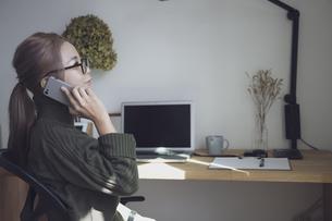 自宅オフィスでリモートワークで電話する女性とデスク用品の写真素材 [FYI04669992]