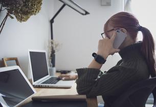 自宅オフィスでリモートワークで電話する女性とデスク用品の写真素材 [FYI04669995]