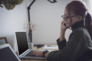 自宅オフィスでリモートワークで働く女性とデスク用品の写真素材 [FYI04669997]