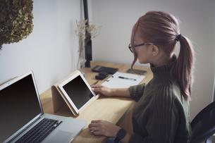 自宅オフィスでリモートワークで働く女性とデスク用品の写真素材 [FYI04669998]