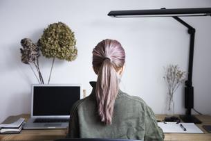 自宅オフィスでリモートワークで働く女性とデスク用品の写真素材 [FYI04670000]