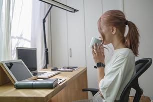 自宅オフィスでリモートワークで働く女性がコーヒーを飲みながら休憩するイメージショットの写真素材 [FYI04670004]
