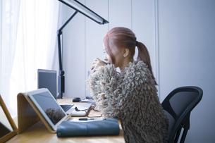 自宅オフィスでリモートワークで働く女性がコーヒーを飲みながら休憩するイメージショットの写真素材 [FYI04670029]