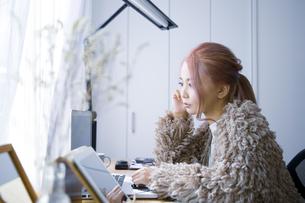 自宅オフィスでリモートワークで働く女性の考える表情の写真素材 [FYI04670034]