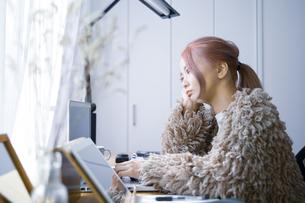 自宅オフィスでリモートワークで働く女性の考える表情の写真素材 [FYI04670035]