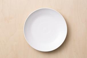 白木の上に置かれた白い皿の写真素材 [FYI04670066]