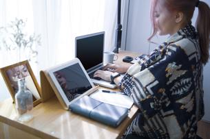 自宅オフィスでリモートワークで働く女性のスマートウォッチをした腕の写真素材 [FYI04670470]
