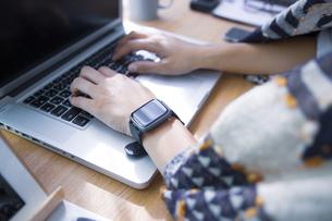 自宅オフィスでリモートワークで働く女性のスマートウォッチをした腕の写真素材 [FYI04670471]