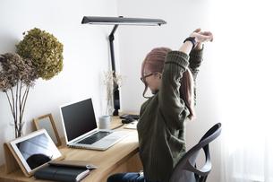 オフィスで伸びのストレッチをして休憩する女性の写真素材 [FYI04670475]