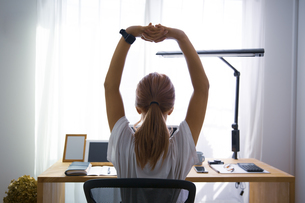 オフィスで伸びのストレッチをして休憩する女性の写真素材 [FYI04670478]