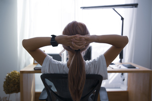 オフィスで伸びのストレッチをして休憩する女性の写真素材 [FYI04670480]