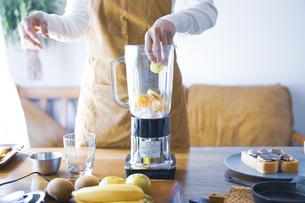 おうちカフェで、フルーツスムージーを作る女性の写真素材 [FYI04670481]